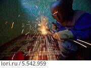 Купить «Сварщик в защитном костюме и маске за работой», фото № 5542959, снято 3 августа 2012 г. (c) Losevsky Pavel / Фотобанк Лори