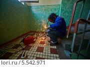 Купить «Сварщик в маске занимается сваркой труб, сидя на ступеньке лестницы», фото № 5542971, снято 3 августа 2012 г. (c) Losevsky Pavel / Фотобанк Лори