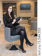 Купить «Деловая женщина в очках сидит на стуле с блокнотом в офисе и улыбается», фото № 5544555, снято 14 февраля 2013 г. (c) Losevsky Pavel / Фотобанк Лори
