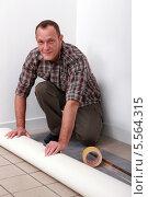 Купить «рабочий собирается стелить линолеум», фото № 5564315, снято 30 ноября 2010 г. (c) Phovoir Images / Фотобанк Лори