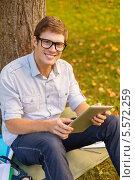 Купить «молодой человек сидит на траве в парке и держит в руках планшетный компьютер», фото № 5572259, снято 15 сентября 2013 г. (c) Syda Productions / Фотобанк Лори