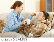 Купить «Девушка ухаживает за больным мужем. Мужчина лежит под пледом на диване, супруга поит его с ложки», фото № 5574879, снято 25 апреля 2018 г. (c) Яков Филимонов / Фотобанк Лори