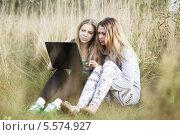 Купить «Две девушки с ноутбуком сидят среди травы», фото № 5574927, снято 28 августа 2013 г. (c) Данил Руденко / Фотобанк Лори