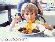 Купить «Испачкавший лицо мальчик с аппетитом ест макароны по-средиземноморски», фото № 5579811, снято 10 июля 2012 г. (c) Юлия Кузнецова / Фотобанк Лори