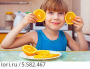 Купить «Мальчик с апельсинами на кухне», фото № 5582467, снято 21 марта 2012 г. (c) Anelina / Фотобанк Лори