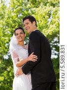 Купить «Romantic newlywed couple standing in park», фото № 5589831, снято 21 ноября 2013 г. (c) Wavebreak Media / Фотобанк Лори