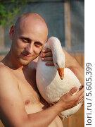 Купить «Молодой мужчина держит гуся», эксклюзивное фото № 5605399, снято 17 июля 2012 г. (c) Вероника / Фотобанк Лори