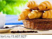 Купить «Круассаны в плетёной тарелке и чашка кофе», фото № 5607827, снято 23 июля 2013 г. (c) Sergey Nivens / Фотобанк Лори