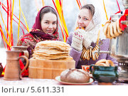 Купить «Девушки за праздничным столом едят угощения. Масленица», фото № 5611331, снято 22 января 2018 г. (c) Елена Ермакова / Фотобанк Лори