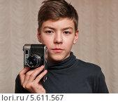 Купить «Мальчик-подросток держит в руках плёночный фотоаппарат ФЭД-5в», эксклюзивное фото № 5611567, снято 10 февраля 2014 г. (c) Игорь Низов / Фотобанк Лори