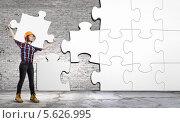 Купить «Девушка-инженер собирает на стене большой пазл», фото № 5626995, снято 18 апреля 2019 г. (c) Sergey Nivens / Фотобанк Лори
