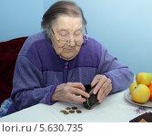 Пожилая бабушка, которая сидит за столом и считает деньги. Стоковое фото, фотограф Шуба Виктория / Фотобанк Лори