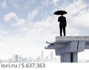 Купить «Молодой бизнесмен в черном костюме стоит под дождем на краю моста», фото № 5637363, снято 27 мая 2019 г. (c) Sergey Nivens / Фотобанк Лори