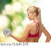Купить «Позитивная девушка тренируется с гантелями и улыбается», фото № 5641575, снято 23 марта 2013 г. (c) Syda Productions / Фотобанк Лори