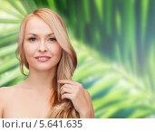 Купить «Привлекательная блондинка с распущенными волосами стоит на фоне пальмы», фото № 5641635, снято 7 января 2014 г. (c) Syda Productions / Фотобанк Лори