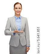 Счастливая деловая женщина в сером костюме показывает что-то на руке. Стоковое фото, фотограф Syda Productions / Фотобанк Лори