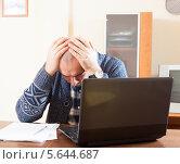 Купить «Грустный мужчина держится за голову сидя за столом на работе», фото № 5644687, снято 21 сентября 2019 г. (c) Дарья Филимонова / Фотобанк Лори