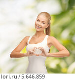 Купить «Девушка улыбается, сложив в форме сердца пальцы на груди», фото № 5646859, снято 23 марта 2013 г. (c) Syda Productions / Фотобанк Лори