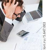 Купить «Взбешенный бизнесмен средних лет смотрит на цифры, схватившись за голову», фото № 5647003, снято 3 октября 2013 г. (c) Syda Productions / Фотобанк Лори