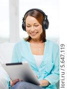 Купить «Счастливая женщина в наушниках держит планшетный компьютер на коленях», фото № 5647119, снято 20 декабря 2013 г. (c) Syda Productions / Фотобанк Лори