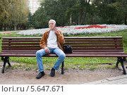 Купить «Пожилой мужчина разговаривает по телефону на лавочке в парке», фото № 5647671, снято 9 сентября 2013 г. (c) Victoria Demidova / Фотобанк Лори