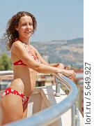 Купить «Молодая женщина в красном купальнике стоит на балконе  в солнечный день», фото № 5649927, снято 11 июля 2012 г. (c) Losevsky Pavel / Фотобанк Лори