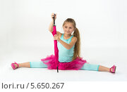 Купить «Радостная девочка в розовой пачке с зонтом в руках сидит на шпагате», фото № 5650267, снято 12 декабря 2012 г. (c) Losevsky Pavel / Фотобанк Лори
