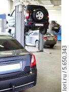 Багажник черной машины в гараже. Четыре автомобиля, подготовленные для диагностики и ремонта. Малая глубина резкости. Стоковое фото, фотограф Losevsky Pavel / Фотобанк Лори