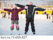 Купить «Мальчик и девочка на коньках стоят, раскинув руки в стороны», фото № 5650427, снято 19 января 2013 г. (c) Losevsky Pavel / Фотобанк Лори
