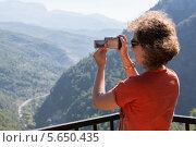 Купить «Женщина фотографирует пейзаж в горах», фото № 5650435, снято 15 июля 2012 г. (c) Losevsky Pavel / Фотобанк Лори