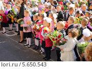 Дети с цветами стоят у школы на линейке 1 сентября, Москва (2012 год). Редакционное фото, фотограф Losevsky Pavel / Фотобанк Лори