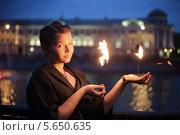 Девушка в чёрной одежде с горящими факелами в руках на фоне ночного города. Стоковое фото, фотограф Losevsky Pavel / Фотобанк Лори