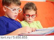 Купить «Девочка и мальчик в очках внимательно делают домашнее задание», фото № 5650855, снято 19 октября 2011 г. (c) Losevsky Pavel / Фотобанк Лори