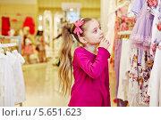 Купить «Маленькая длинноволосая девочка с интересом разглядывает стенд с детской одеждой в магазине», фото № 5651623, снято 17 марта 2012 г. (c) Losevsky Pavel / Фотобанк Лори