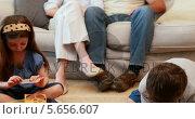 Купить «Young siblings doing arts and crafts on the rug while parents watch», видеоролик № 5656607, снято 22 июля 2019 г. (c) Wavebreak Media / Фотобанк Лори
