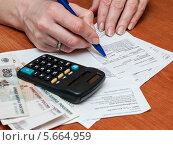 Купить «Женщина рассчитывает семейный бюджет на коммунальные расходы», эксклюзивное фото № 5664959, снято 3 марта 2014 г. (c) Игорь Низов / Фотобанк Лори