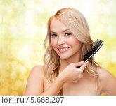 Купить «Очаровательная блондинка расчесывает волосы и улыбается», фото № 5668207, снято 7 января 2014 г. (c) Syda Productions / Фотобанк Лори