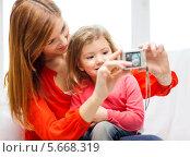 Купить «Мама и маленькая девочка фотографируются на фотоаппарат дома», фото № 5668319, снято 17 января 2014 г. (c) Syda Productions / Фотобанк Лори