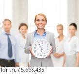 Купить «Деловая женщина с большими настенными часами на фоне коллег в офисе», фото № 5668435, снято 7 января 2014 г. (c) Syda Productions / Фотобанк Лори