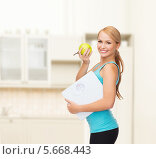 Купить «Спортивная девушка на кухне с весами и яблоком», фото № 5668443, снято 7 января 2014 г. (c) Syda Productions / Фотобанк Лори