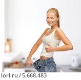 Купить «Стройная девушка демонстрирует джинсы большого размера», фото № 5668483, снято 23 марта 2013 г. (c) Syda Productions / Фотобанк Лори