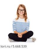 Купить «Счастливая девочка в очках сидит на полу», фото № 5668539, снято 31 июля 2013 г. (c) Syda Productions / Фотобанк Лори
