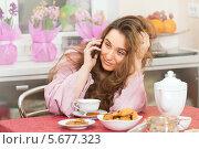 Купить «Девушка в розовом халате с мобильным телефоном за столом на кухне», фото № 5677323, снято 2 марта 2014 г. (c) Юлия Кузнецова / Фотобанк Лори
