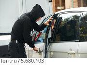 Купить «Автоугонщик открывает дверь автомобиля», фото № 5680103, снято 26 июня 2013 г. (c) Дмитрий Калиновский / Фотобанк Лори