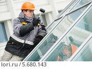 Купить «Рабочий во время установки окна», фото № 5680143, снято 12 февраля 2014 г. (c) Дмитрий Калиновский / Фотобанк Лори