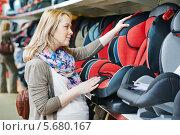 Купить «Женщина выбирает в магазине детское автомобильное сиденье», фото № 5680167, снято 23 ноября 2013 г. (c) Дмитрий Калиновский / Фотобанк Лори