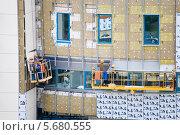 Купить «Рабочие монтируют панели навесного вентилируемого фасада здания», эксклюзивное фото № 5680555, снято 11 августа 2012 г. (c) Владимир Чинин / Фотобанк Лори