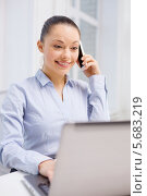 Купить «Молодая женщина разговаривает по телефону и смотрит на экран ноутбука», фото № 5683219, снято 8 декабря 2013 г. (c) Syda Productions / Фотобанк Лори