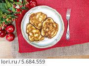 Купить «Оладья с яблоками на керамической тарелке на красной скатерти», фото № 5684559, снято 19 февраля 2019 г. (c) BE&W Photo / Фотобанк Лори