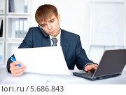 Молодой бизнесмен ведет переговоры по телефону в офисе. Стоковое фото, фотограф Viktor Gladkov / Фотобанк Лори